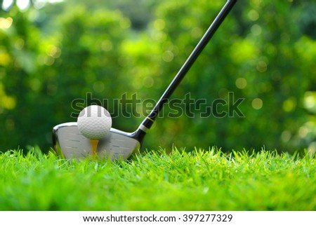 Golf ball on green grass ready to be struck on golf course background - stock photo