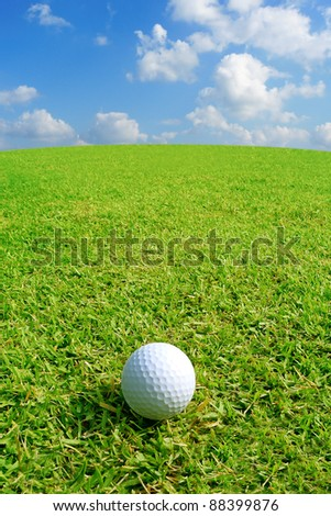 Golf ball on green grass with clear blue sky - stock photo
