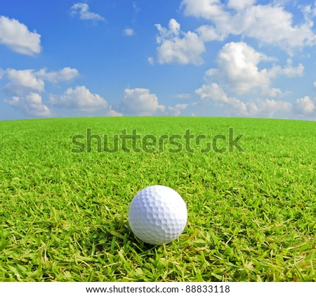 Golf ball on green grass with clear blue sky