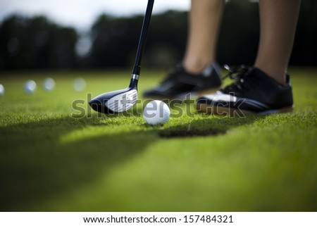 Golf ball on green meadow, driver  - stock photo
