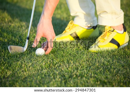 Golf ball on green tee. Man in yellow training shoes arranging golf ball with his hand.