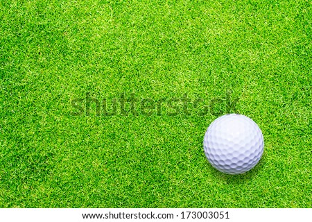 Golf ball on green texture background - stock photo