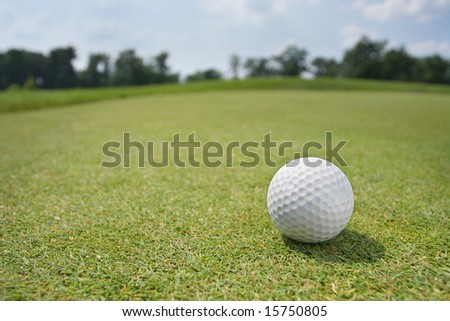 Golf Ball on Green. Wide angle against background of trees and sky. - stock photo