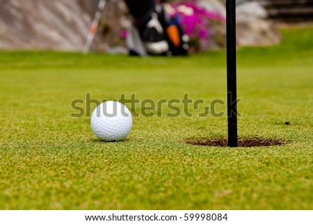 Golf ball on green with a hole. Shallow depth of field. Focus on the ball and the hole. - stock photo