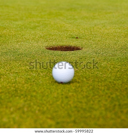 Golf ball on green with a hole. Shallow depth of field. Focus on the hole. - stock photo