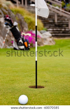 Golf ball on green with flag. Shallow depth of field. Focus on the flag. - stock photo