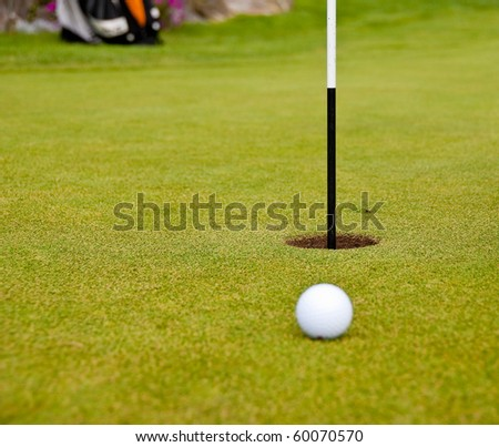 Golf ball on green with flag. Shallow depth of field. Focus on the hole. - stock photo