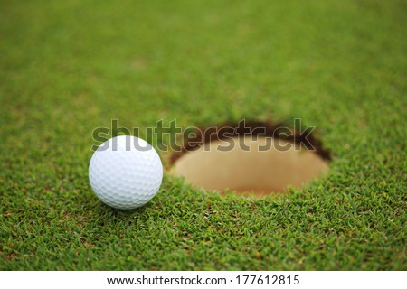 golf ball on lip of cup - stock photo