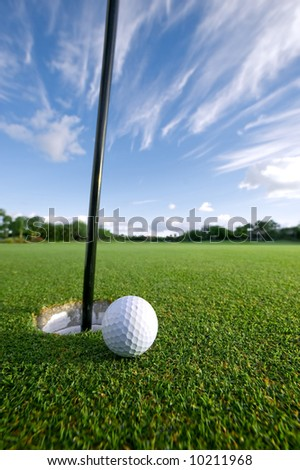 golf ball on lip of cup at green - stock photo