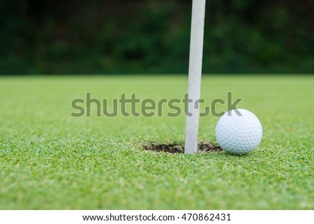 golf ball on lip of cup, copy space on Left side.