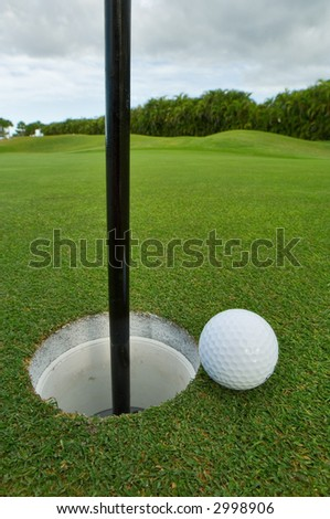 golf ball on lip of cup of immaculately groomed green - stock photo
