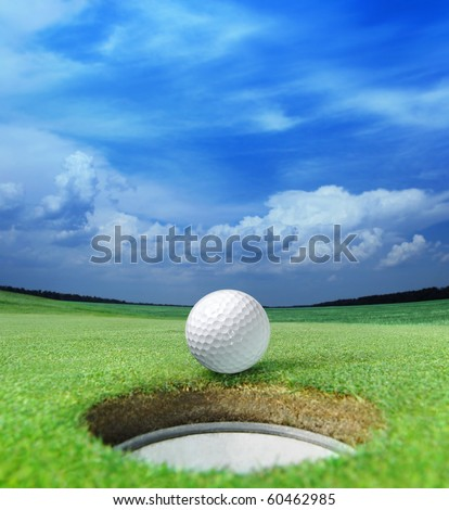 golf ball on lip of cup of lovely beautiful golf course - stock photo