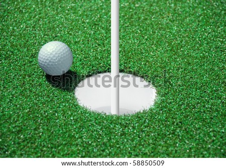 golf ball on lip of cup of lovely tropical golf course - stock photo