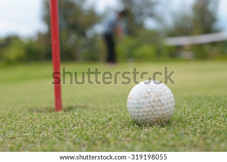 Golf ball on lip of hole - stock photo