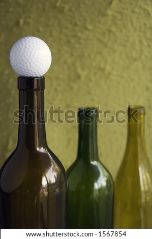 Golf ball on mouth of empty wine bottle (focus on golf ball) - stock photo