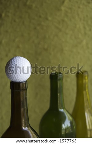 Golf ball on mouth of wine bottle (focus on golf ball in foreground) - stock photo
