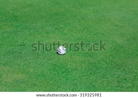 Golf ball on perfect wavy green ground on a golf course - stock photo