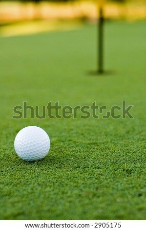 Golf ball on putting green next to hole