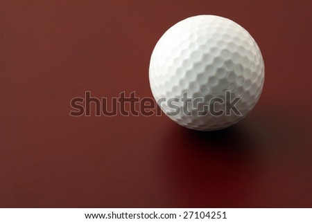golf ball on red surface - stock photo