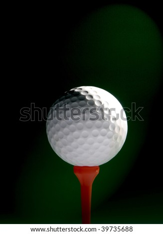 Golf ball on red tee over black