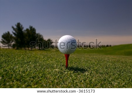 Golf ball on red tee with scenic background - stock photo