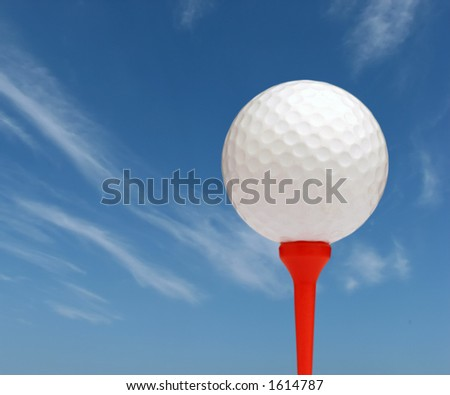 Golf ball on red tee with sky background