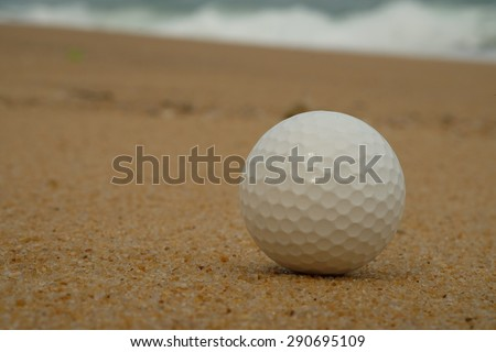Golf ball on sand with the ocean background