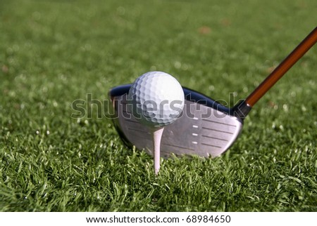 Golf ball on tee about to be hit by a driver. - stock photo