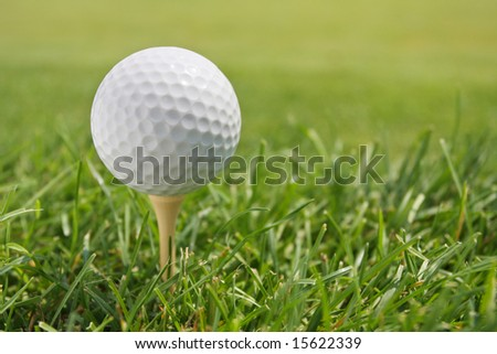 Golf Ball on Tee against grass with shallow depth of field. - stock photo