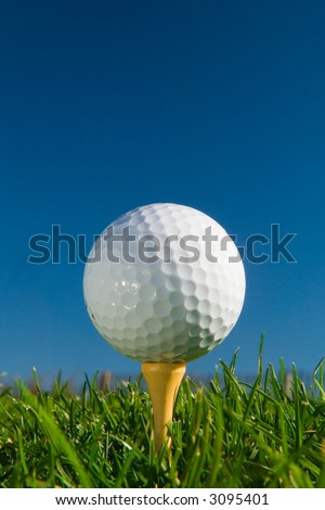 golf ball on tee from ground level, deep blue sky for copy - stock photo