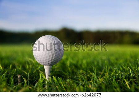 Golf ball on tee. Green grass, blue sky. - stock photo