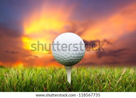 Golf ball on tee. Green grass, sunset. - stock photo