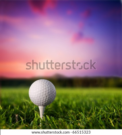 Golf ball on tee. Green grass, sunset. - stock photo