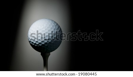 Golf ball on tee illuminated by a ray of light on black background. Space for text