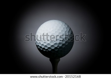 Golf ball on tee illuminated by a ray of light on black background. Space for text - stock photo