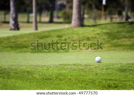 Golf ball on tee in a beautiful green grass golf course. Photographed with shallow DOF (Lifestyle concept) - stock photo