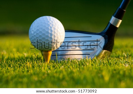 Golf ball on tee in front of driver on a gold course - stock photo