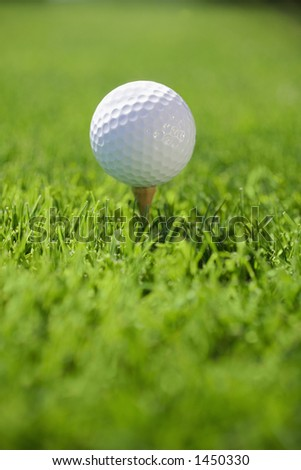 Golf Ball on tee in grass - stock photo