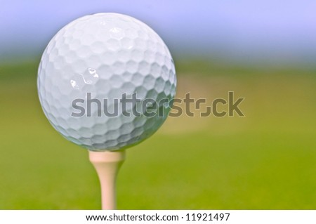 golf ball on tee isolated against out of focus fairway - stock photo