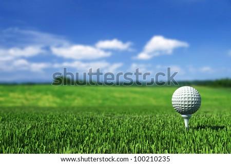 golf ball on tee on the  green grass - stock photo