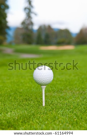 Golf ball on tee over a blurred green, bunker and path. Shallow depth of field. Focus on the ball. - stock photo