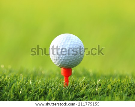 Golf ball on tee over the green grass background - stock photo