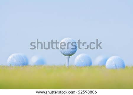 golf ball on tee surrounded by other golf balls out of focus - stock photo