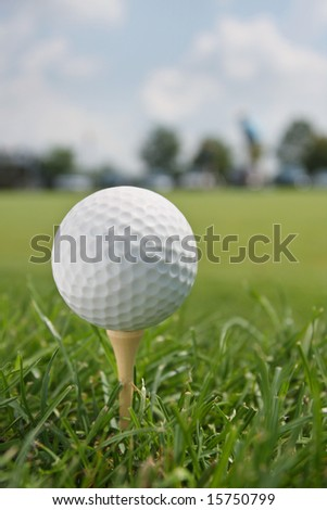 Golf Ball on Tee with blurred fairway and trees in background. - stock photo