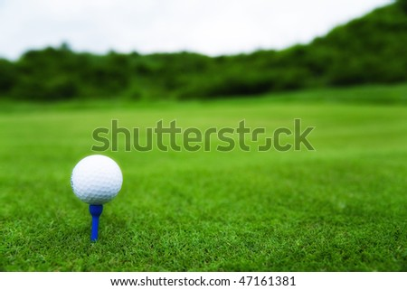 Golf ball on tee with blurred golf course in the background. - stock photo