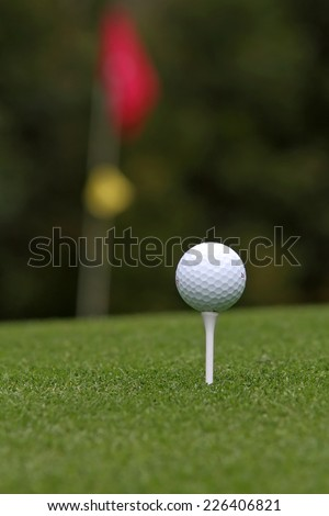 Golf ball on tee with flag stick in background - stock photo
