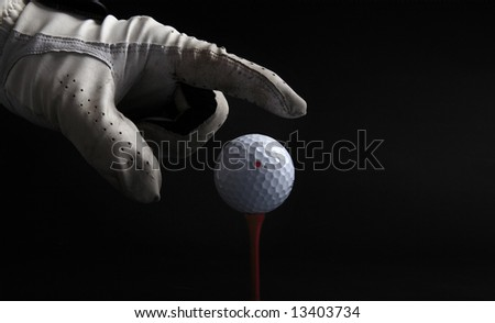 golf ball on tee with hand with glove going for the ball over black background - stock photo