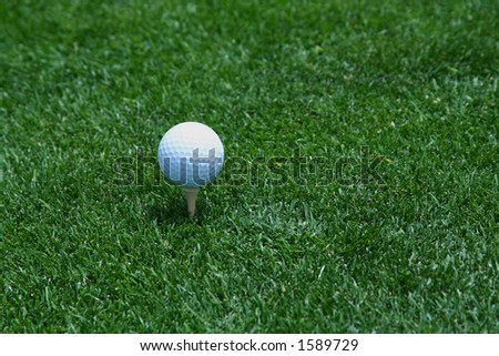 Golf ball on tee with space for logo on golf ball - stock photo