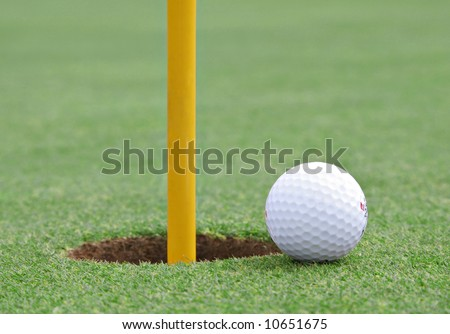 golf ball on the edge of the cup, extremely shallow DOF - stock photo