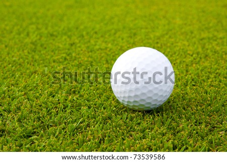 Golf ball on the green grass waiting for you to drives it out to hit your goal - stock photo